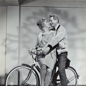 Martha Hyer and Danny Kaye ride a bike, kickstand down.