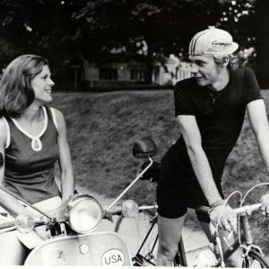 Dennis Christopher rides a bike, Robyn Douglass rides a Vespa.