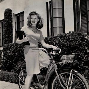 Barbara Britton rides a bike, carries a script.