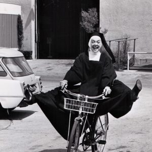Rosalind Russell rides a bike, habitually.