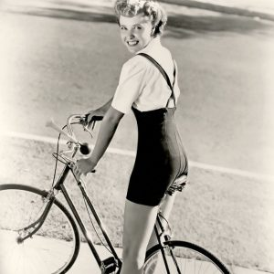 Laraine Day rides a bike.