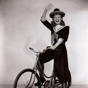 Mona Freeman rides a bike, gives a wave.
