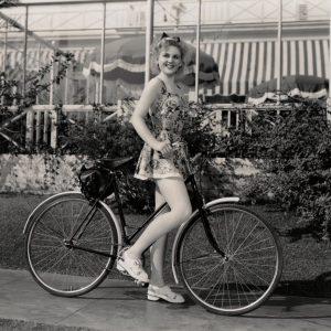 Elaine Morey, aka Janet Warren, rides a bike.