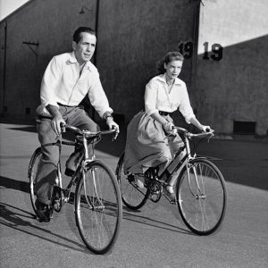 Humphrey Bogart and Lauren Bacall ride bikes.