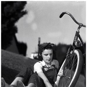 Judy Garland checks a bike tire.
