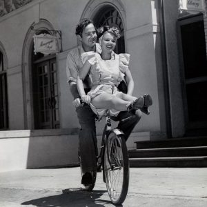 Broderick Crawford and Jane Frazee ride a bike.
