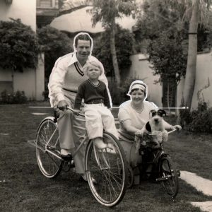 Joe E. Brown, Mary Elizabeth Brown, Kathryn Brown and fox terrier Brown ride bikes.