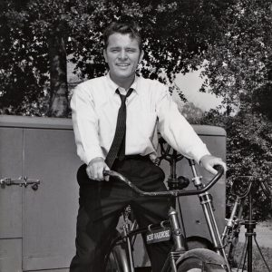 Richard Burton rides a bike, courtesy of Men's Wardrobe.
