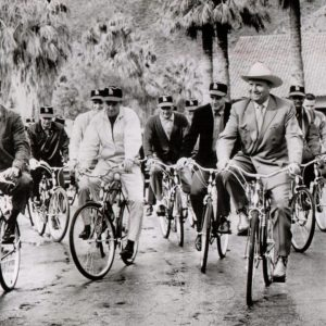 Gene Autry rides a bike with Leon Wagner, Ken McBride, Joe Nuxhall, Dick Simpson, Felix Torres, Jim Fregosi and other members of the 1962 Los Angeles Angels. PEDAL-PUSHERS: In Palm Springs, Calif., yesterday – Gene Autry, right foreground, co-owner of the Los Angeles Angels, led the new American League squad from their hotel to the ball park two miles away for their first spring workout. Fred Haney, general manager, had ordered the bicycle riding. – February, 22, 1962
