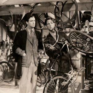 Robert Taylor brings a bike in for repair. Ronald Shiner assesses the damage.