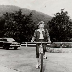 June Allyson rides a bike.