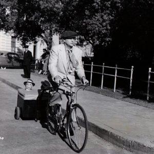 Edgar Bergen and Charlie McCarthy ride a bike. Mortimer Snerd, in the shadows, too.