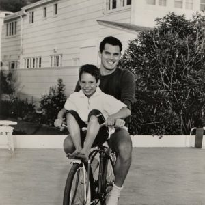 Jeffrey Hunter and Christopher Hunter ride a bike.