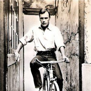 Jean-Louis Trintignant rides a bike.