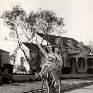 Leslie Brooks and Neila Hart ride a bike.