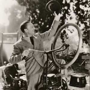 "Warren William rides a bike.  ""ON A SPIRITED REARING STEED – Warren William, who makes his debut as a Mae West leading man in her latest starring picture, ""Go West Young Man,"" laid aside his suave sophistication while on a location trip for scenes in the new film – and here's the result. William's prowess as a bicyclist speaks for itself."""