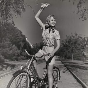 June Lang rides a bike, waves a hanky.