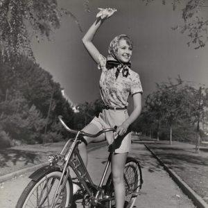 June Lang rides a bike, waves a hanky.