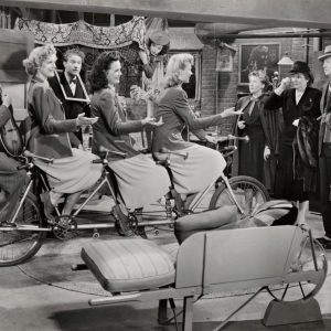 Alvino Rey and the King Sisters ride a bike. Margaret Dumont looks on.