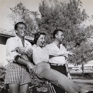 Leonore Cohn rides a bike, Victor Mature and Beldon Katleman stand at the ready.