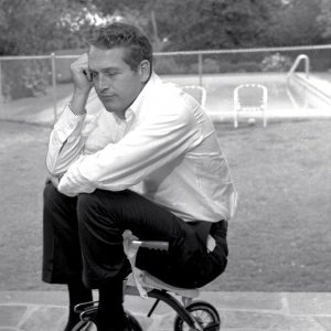 Paul Newman rides a trike, meditatively.