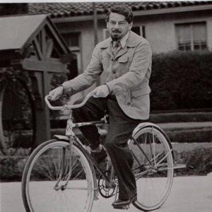 Paul Muni rides a bike.