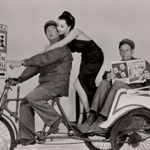 Harvey Lembeck and Mari Blanchard ride a pedicab, Tom Ewell reads Love Confessions.