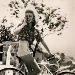Ginger Rogers rides a bike, wears a hat, gives a shout. An RKO Radio Pictures postcard.