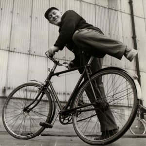 """Alec Guinness mounts a bike. MY GOODNESS…….. IT'S GUINNESS AGAIN Alec mounts the bicycle he uses in the film """"The Horse's Mouth."""" During the current London bus strike he might find this studio prop a handy vehicle for getting to and from his work.Pictorial Press Ltd., July25, 1957"""