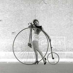 Frances Pidgeon models a bike, Ken Russell takes the photo, Penny Farthing on loan from The Troubadour coffee house, London, 1956.