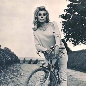 Sharon Tate rests a bike.