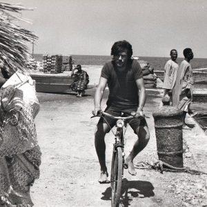 Alain Delon rides a bike.