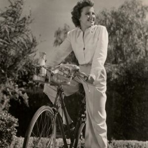 Laraine Day rides a bike – home from the market.