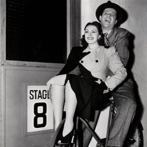 "Nancy Kelly and Robert Cummings ride a bike. ""Well, here's one way to get to work. Robert Cummings pedals Nancy Kelly to the set of Universal's ""One of the Boston Bullertons,"" in which they play the romantic leads."" – Universal Pictures, 1940"