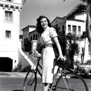 Marguerite Chapman rides a bike.