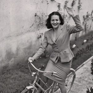 "Yvonne Sanson rides a bike, waves ""Ciao!"""