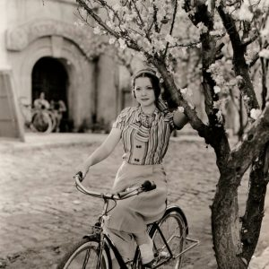 Sylvia Sidney rides a bike, holds a tree.