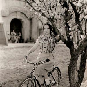 Sylvia Sidney rides a bike, holds a tree.