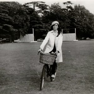 Nancy Kwan rides a bike.