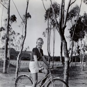 Janis Carter rides a bike.