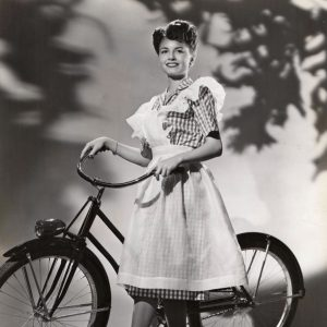 Janet Blair models a bike, ginghamly.