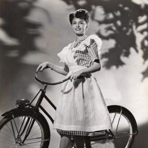 Janet Blair models a bike, ginghamly.