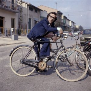 Roberto Benigni rests on a bike.