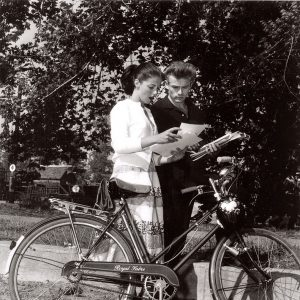 Pier Angeli and James Dean read a script, rest a bike.