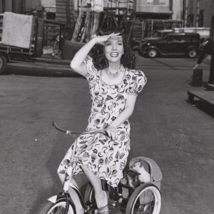 Lupe Vélez and Chihuahuas ride a trike.