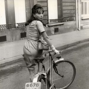 Leslie Caron walks a bike.
