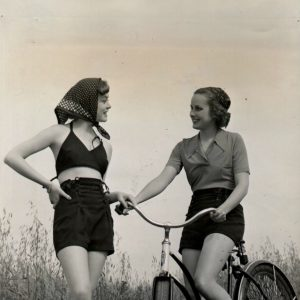 "Libby Harben rides a bike. Ruth Martin wears ""a navy gabardine playsuit, trunks and bra-top, and ties her hair peasant fashion, beneath a dotted kerchief."""