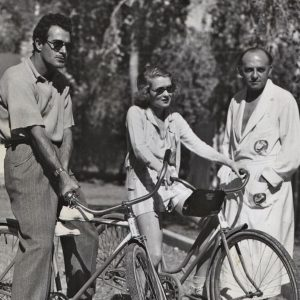"Gilbert Roland and Constance Bennett ride bikes. Harry Cohn, ""genial president of Columbia Pictures,"" rides a bathrobe. On the grounds of the Desert Inn, Palm Springs, November, 1933."