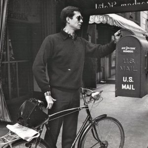 Anthony Perkins walks a bike, mails a letter. New York, 1964.