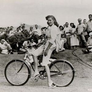 Jane Russell rides a bike, side-saddle.